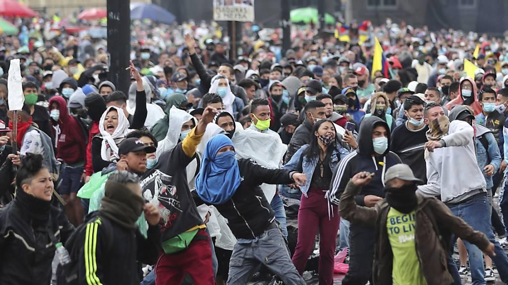 Demonstranten in Bogota werfen Steine während eines Protests gegen eine von der kolumbianischen Regierung vorgeschlagenen Steuerreform. Foto: Fernando Vergara/AP/dpa