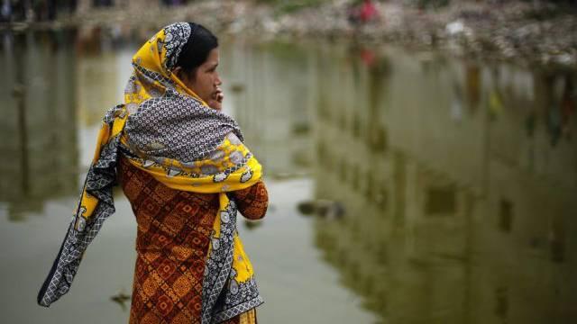 Eine Arbeiterin blickt über das Gelände, worauf die Fabrik stand