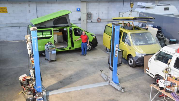 Urs Egli (Bildmitte) steht vor einem von ihm ausgebauten Nissan Camper, den man auch mieten kann. Rechts steht sein Mitarbeiter Rolf Bolliger bei der Montage eines Aufstelldaches in einem VW-Bus. Toni Widmer