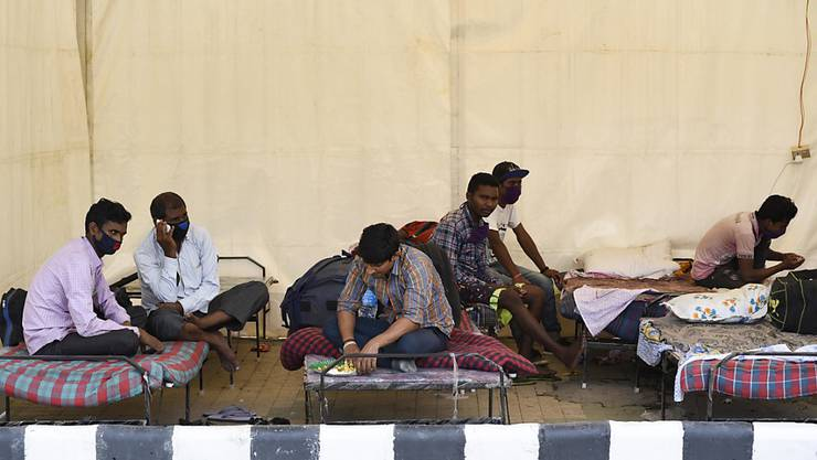 Wanderarbeiter warten im nordostindischen Guwahati auf den Bus, der sie in ihre Heimatorte bringen soll. Foto: David Talukdar/ZUMA Wire/dpa