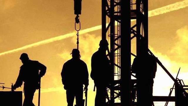 Bauarbeiter stehen bei Sonnenaufgang auf einer Baustelle.