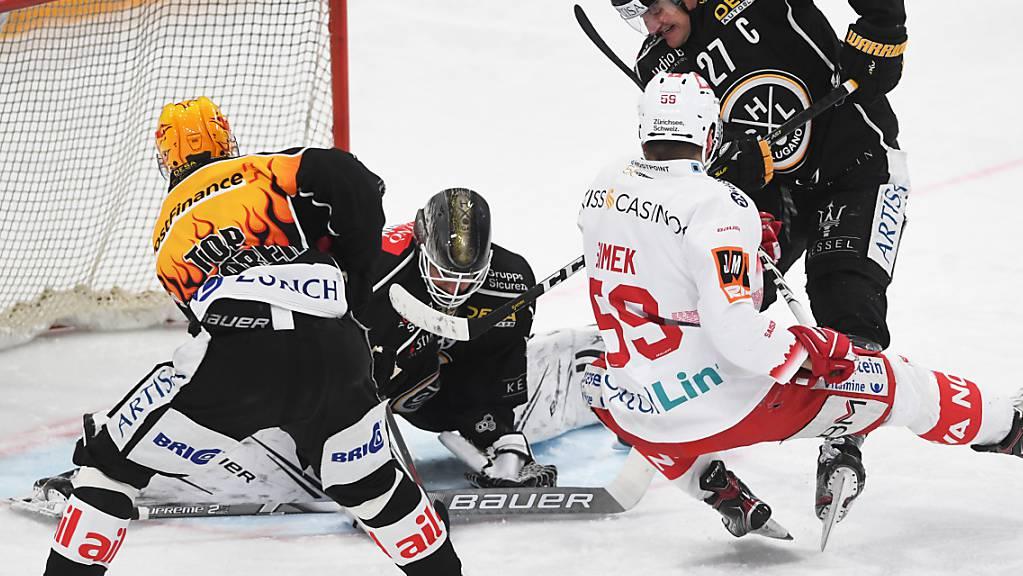 Luganos Goalie Sandro Zurkirchen kommt hier gegen den Laker Juraj Simek (Zweiter von rechts) in Bedrängnis.