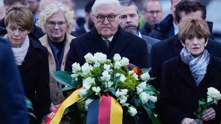 Bundespräsident Frank-Walter Steinmeier legt in Hanau einen Blumenstrauss nieder.