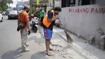 Coronastrafe in Indonesien: Wer keine Maske trägt, muss die Strasse kehren – in einer leuchtend-orangen Weste mit der Aufschrift «Verletzer des Gesundheitsprotokolls».