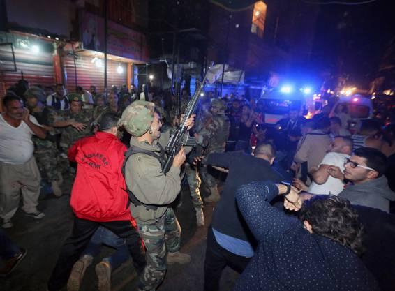 Ein libanesischer Soldat feuert in die Luft um Menschen zu vertreiben, die um eine am Boden liegenden Mann herum stehen.