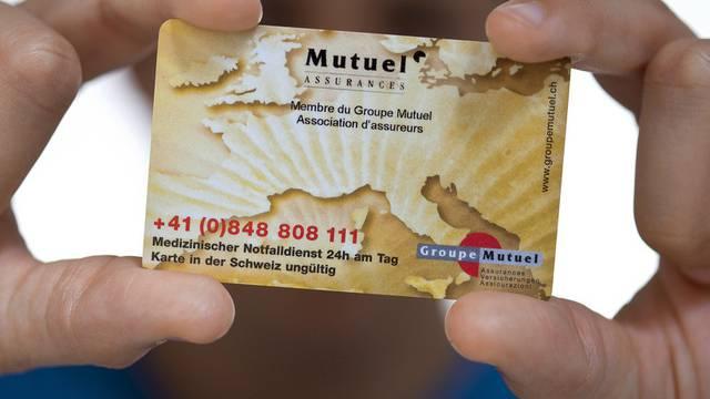 Ein Mann präsentiert eine Versicherungskarte der Krankenkasse Groupe Mutuel (Archiv)
