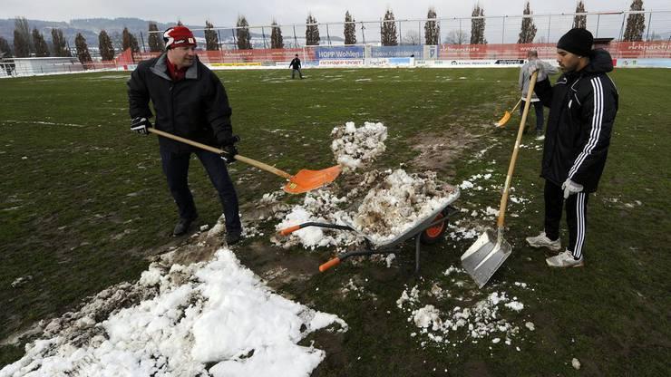 Funktionäre und Freiwillige räumen den Schnee im Stadion Niedermatten weg – der Rasen leidet stark, das soll sich mit einem Kunstrasen ändern