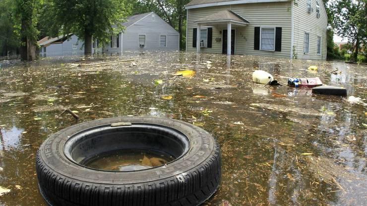 Abfall treibt an überfluteten Häusern vorbei