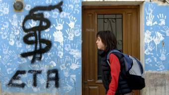 Haus in der Stadt Pamplona mit dem Abdruck weisser Hände als Symbol gegen den Terror der ETA – übersprüht mit dem ETA-Symbol.