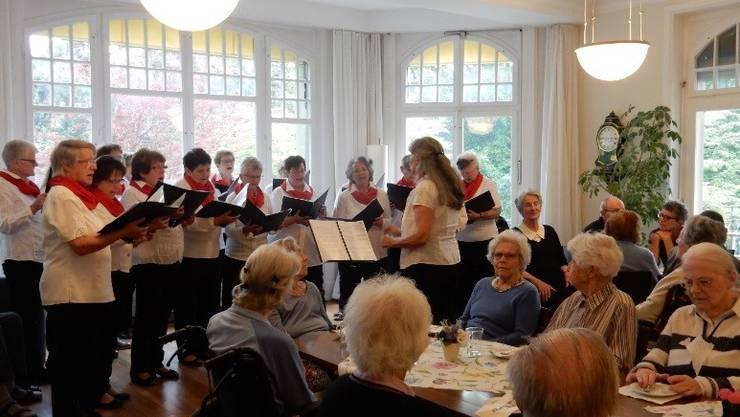 Die Bewohnerinnen und Bewohner vom Wildermettpark hören dem Chor sehr aufmerksam zu.