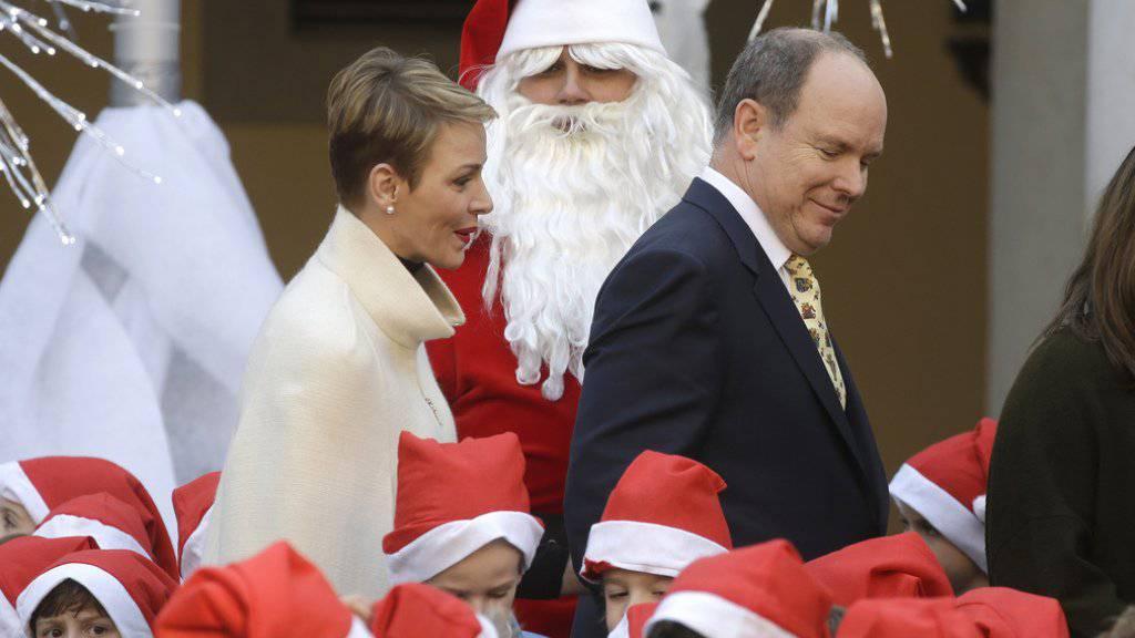 Ein royales Paar in Festtagsstimmung: Fürst Albert II. und seine Frau Charlène von Monaco, hier von kleinen und grossen Samichläusen umgeben, posierten für das offizielle Weihnachtsfoto vor einem Greifvogel (Archiv).