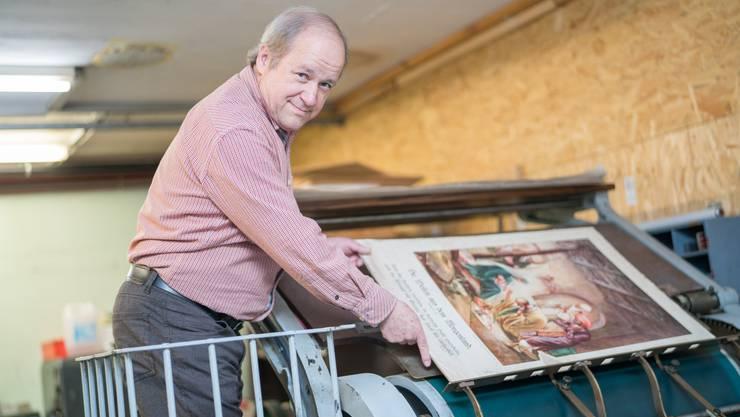 Bruno Altherr zeigt an der alten Steindruckpresse, wie das Bild «eine Reise aus dem Morgenland» gedruckt worden ist.