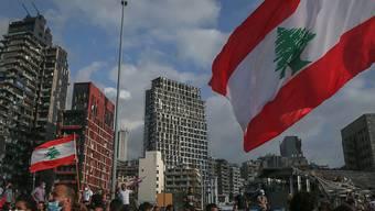 Regierungskritische Demonstranten nehmen an Demonstranten mit der Fahne des Libanon Mitte August bei einem Trauermarsch für die Opfer der verheerenden Explosion von Beirut. Foto: Marwan Naamani/dpa