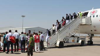 Jemenitische Gefangene, die von Huthis festgehalten wurden, verlassen nach ihrer Ankunft an einem Flughafen in Aden das Flugzeug. Der großangelegte zweitägige Austausch von Kriegsgefangenen zwischen den Konfliktparteien im Jemen ist erfolgreich beendet worden. Foto: Wail Shaif/dpa