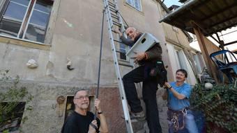 Gesichert von zwei Helfern, steigt Vogelschützer Kurt Bänteli auf eine Leiter, um unter dem Giebel eines Hinterhofhauses einen Nistkasten für Mauersegler (kleines Bild) aufzuhängen. Foto: Juri Junkov