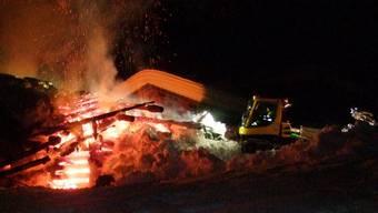Spektakuläre Löschaktion in Klosters GR: Eine Pistenmaschine schiebt Schnee auf einen brennenden Stall.