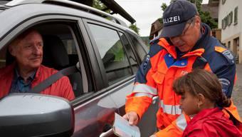 Polizist Markus Steiner kontrolliert gemeinsam mit einer Erstklässlerin einen Ausweis.  az Archiv Peter Siegrist