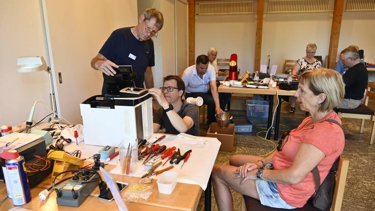 Peter und Sascha Nussbaumer versuchen, die Kaffeemaschine von Margreth Flury zu öffnen