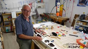 Arnold Hächler in seiner Werkstatt, die Wände voller Segel, und immer eine Arbeit auf der Werkbank.