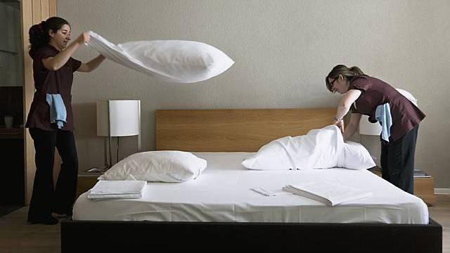 Zwei Angestellte machen in einem Hotelzimmer das Bett (Symbolbild, Archiv)