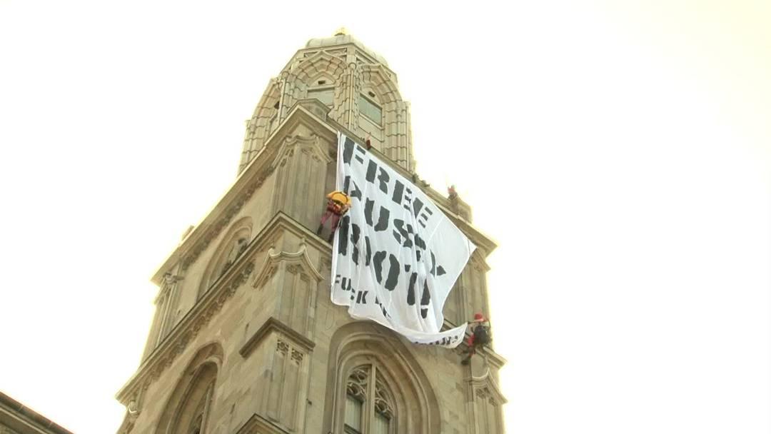 """Das """"Freie Punk Komitee"""", das sich vornehmlich aus Künstlern zusammensetzt, demonstriert in Zürich für die Freilassung der drei verurteilten Pussy-Riot-Aktivistinnen in Russland: am Grossmünster wurde von Kletterinnen ein grossformatiges Plakat entfaltet und die Parole """"Fuck Putin"""" skandiert."""