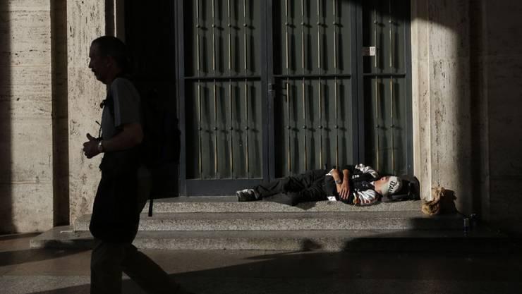 Ein Obdachloser schläft vor einem Gebäude in Rom (Symbolbild/Archiv)