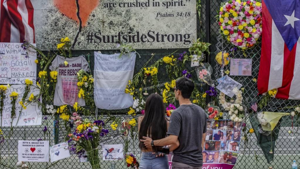 Erinnerungen, persönliche Gegenstände und Blumen sind an der Surfside Wall of Hope  Memorial zu sehen. Zwei Wochen nach dem Einsturz eines Wohnhauses bei Miami besteht kaum noch Hoffnung, Überlebende in den Trümmern zu finden. Man gehe nun von einer Rettungs- zu einer Bergungsaktion über.