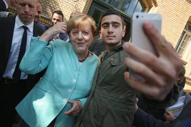 Das Bild des Selfies ging um die Welt: Anas Modamani mit Kanzlerin Merkel in einem Flüchtlingsheim in Berlin-Spandau am 10. September 2015. (Bild Sean Gallup/Getty)