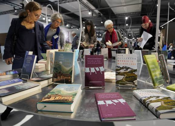 epa07927173 Visitors look at books at the book fair Frankfurter Buchmesse 2019, in Frankfurt am Main, Germany, 17 October 2019. The 71st edition of the international Frankfurt Book Fair, described as the world's most important fair for the print and digital content business, runs from 16 to 20 October and gathers authors, writers and celebrities from all over the world. This year's Guest of Honour country is Norway. EPA/RONALD WITTEK