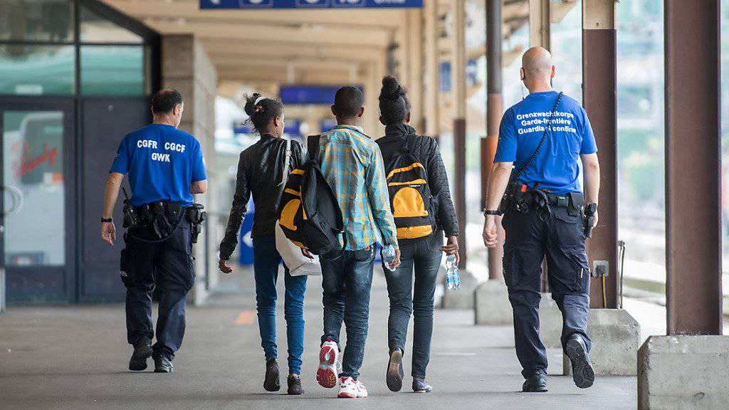 Ein Grenzwaechter begleitet Fluechtlinge, am Dienstag, 12. Juli 2016, auf dem Bahnhof in Chiasso. (KEYSTONE/Ti-Press/Francesca Agosta)