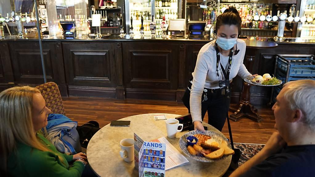 Eine Kellnerin bringt zwei Gästen einem Pub in Newcastle eine Mahlzeit an den Tisch. Die Menschen in weiten Teilen Großbritanniens haben wieder deutlich größere Freiheiten. Foto: Owen Humphreys/PA Wire/dpa