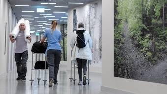 Jede Patientin und jeder Patient erhält für den Umzug eine Begleitperson zugeteilt. Gemeinsam gehts durch die Korridore des Neubaus. Die Fotos an der Wand stammen von der Künstlerin Renate Buser, die als Chefarzt-Tochter auf der Barmelweid aufgewachsen ist.