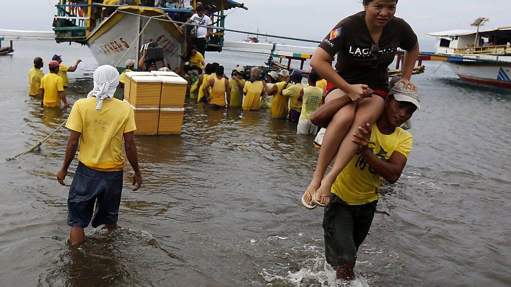 Helfer bringen Überlebende des Unglücks an Land.