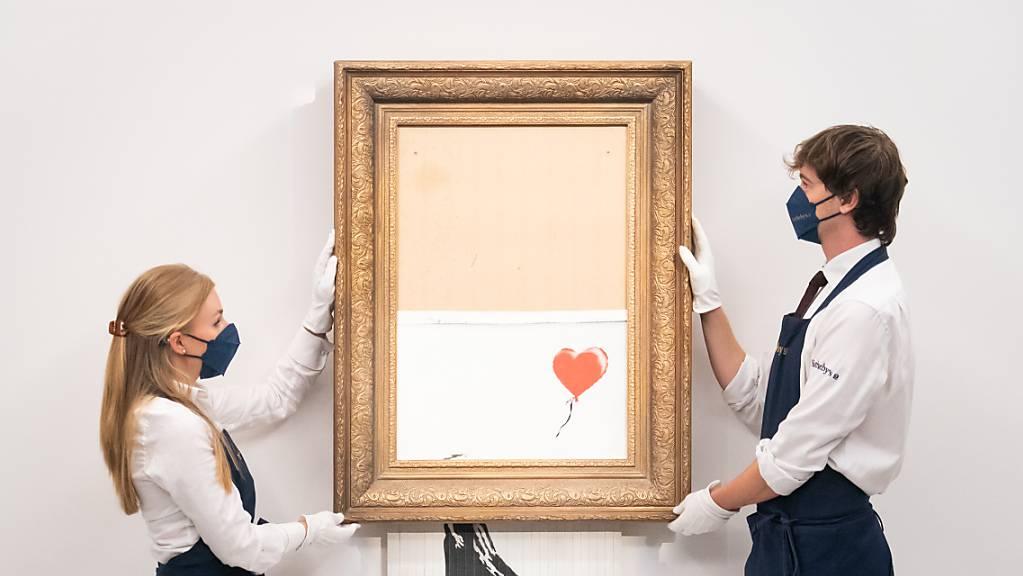 Das während einer Kunstauktion geschredderte Banksy-Bild «Girl with Balloon» wird erneut versteigert. Das Londoner Auktionshaus Sotheby's rechnet bei der Auktion am 14. Oktober mit einem Erlös von vier bis sechs Millionen Pfund (4,66 bis 7 Mio Euro) für das Nild. Foto: Dominic Lipinski/PA Wire/dpa
