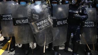 Polizisten stehen mit Mundschutz und Schutzschildern auf der Straße vor der Residenz des Premierministers. Hunderte Menschen haben dafür demonstriert, dass die Regierung die Maßnahmen aufgrund der Corona-Pandemie verstärkt und die Testzahlen erhöht. Foto: Skanda Gautam/ZUMA Wire/dpa