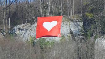 Nun hängt am Born eine Herz-Fahne.