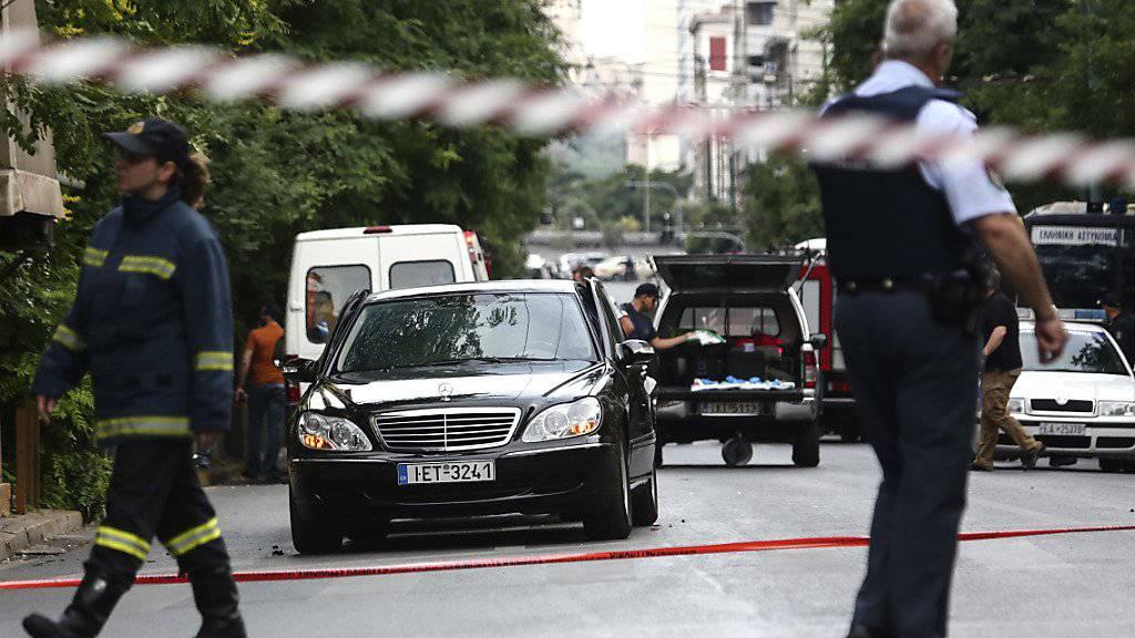Rettungsdienste am Anschlagsort. Der frühere griechische Ministerpräsident Papademos wurde in seinem Auto durch eine Briefbombe verletzt. Er soll ausser Lebensgefahr sein.