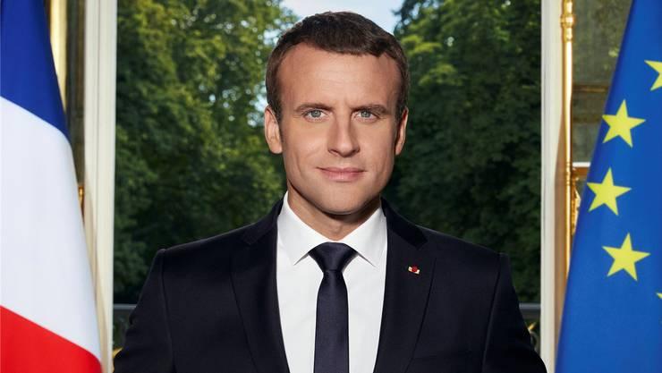 Emmanuel Macron posiert vor den Flaggen Frankreichs und der EU. Das ganze Porträt sehen Sie weiter unten.