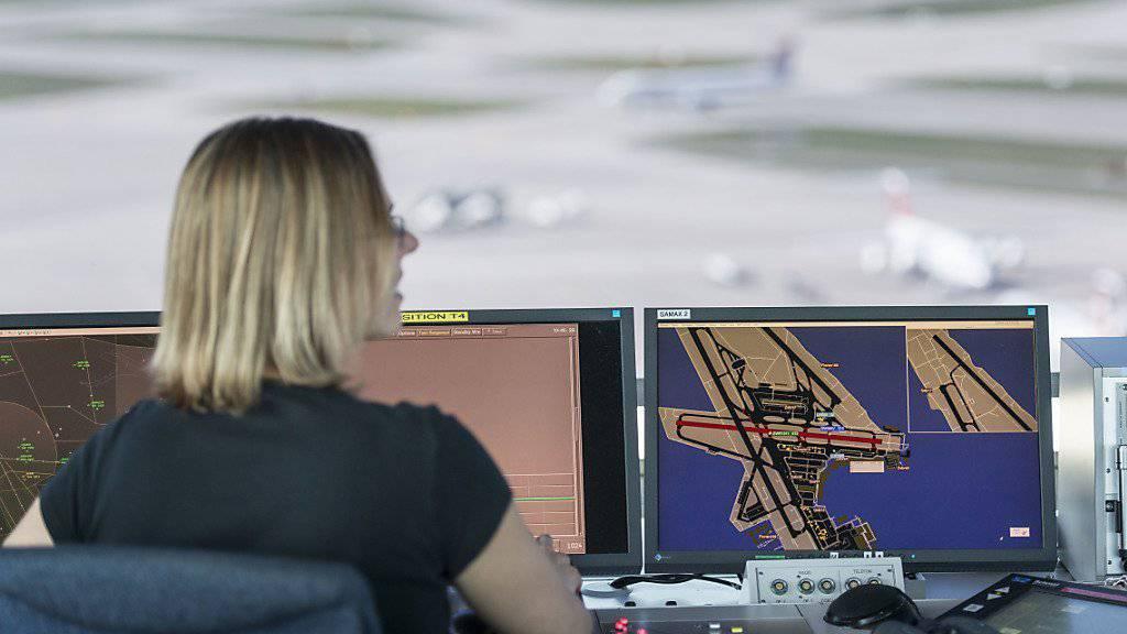 Eine Mitarbeiterin von Skyguide kontrolliert im Tower des Flughafen Zürich die Monitore und hat Blick auf das Flugfeld (Archiv)