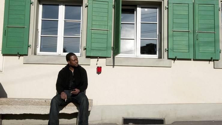 Asylbewerber aus Somalia raucht eine Zigarette vor Unterkunft in Lausanne.