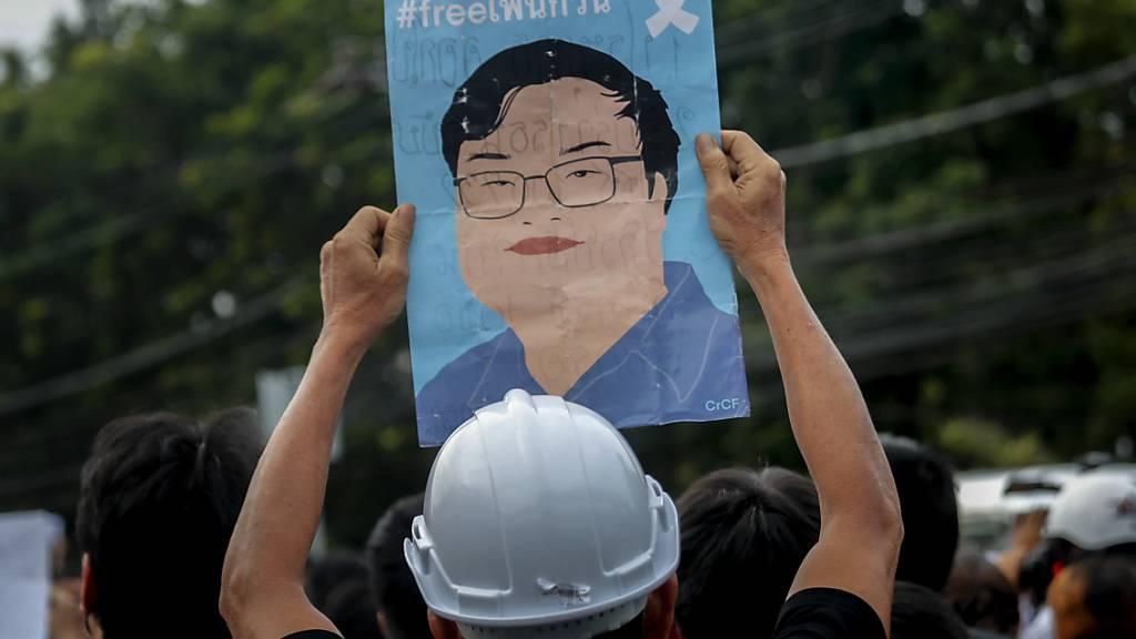 Ein Demonstrant in Bangkok zeigt ein Plakat mit einem Bild des kürzlich inhaftierten Protestführers Parit Chiwarak. Foto: Sakchai Lalit/AP/dpa