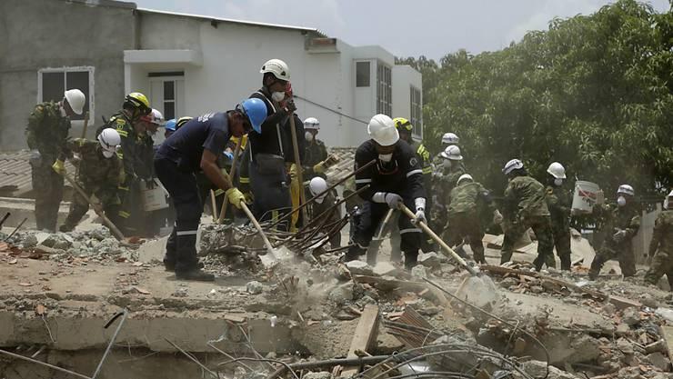 Rettungsarbeiter suchen nach dem Gebäudeeinsturz nach Opfern.