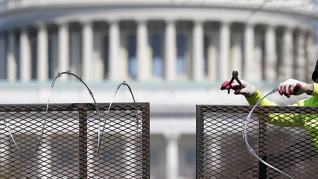 Ein Arbeiter entfernt den Stacheldraht von einem Sicherheitszaun auf dem Capitol Hill. Zweieinhalb Monate nach der Erstürmung des Kapitols durch Anhänger des damaligen US-Präsidenten Trump sind vier führende Mitglieder der rechtsradikalen Gruppe «Proud Boys» angeklagt worden. Foto: Patrick Semansky/AP/dpa