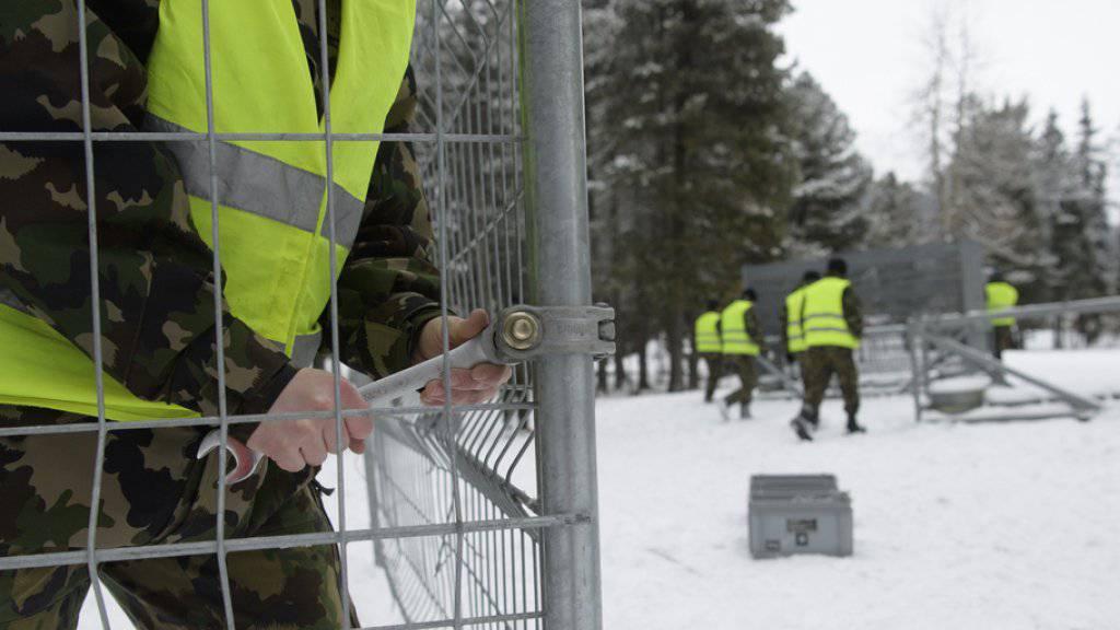 Angehörige der Schweizer Armee errichten im Kurpark des Davoser Kongresszentrums einen Zaun für das WEF.