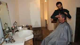 Herencoiffeur Samir Iseini hat seinen Salon einfach eingerichtet. Hier schneidet er einem bartlosen Kunden die Haare. bA