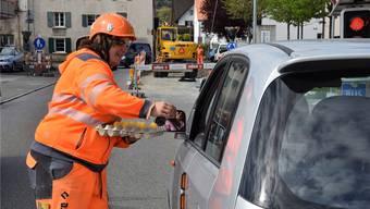 Beatrice Wyssen verteilt den wartenden Autofahrern gelbe Ostereier. MHU