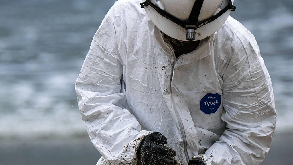 Ein Arbeiter in einem Schutzanzug säubert einen Strandabschnitt. Foto: Jason Ryan/ZUMA Press Wire Service/dpa