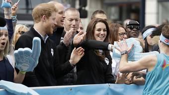 Volksnah: Prinz William, Ehefrau Kate und Prinz Harry unterstützen die Marathonläufer mit Handschlägen, einer Umarmung oder einem Becher Wasser.