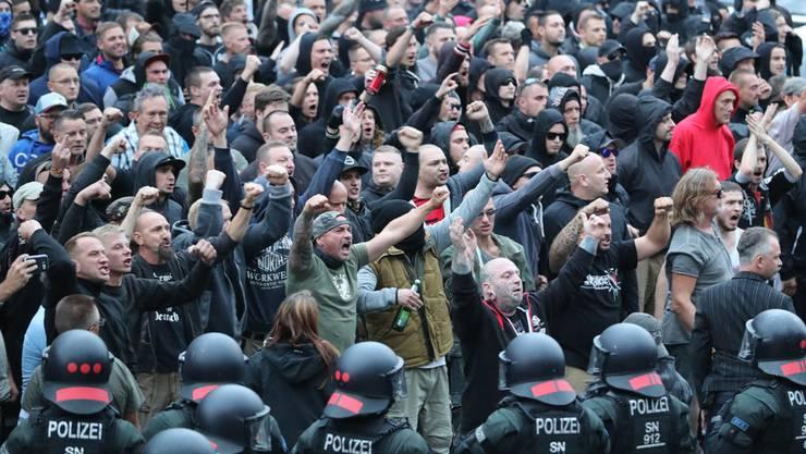 Polizisten stehen in der Chemnitzer Innenstadt am Karl-Marx-Monument bei einer Kundgebung der rechten Szene, um ein Aufeinanderprallen von rechten und linken Gruppen zu verhindern.