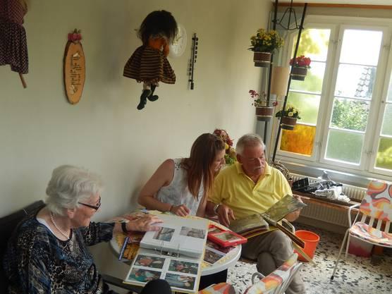 Elsbeth Adam stöbert gemeinsam mit ihrem Sohn und ihrer Enkeltochter in alten Fotobüchern.